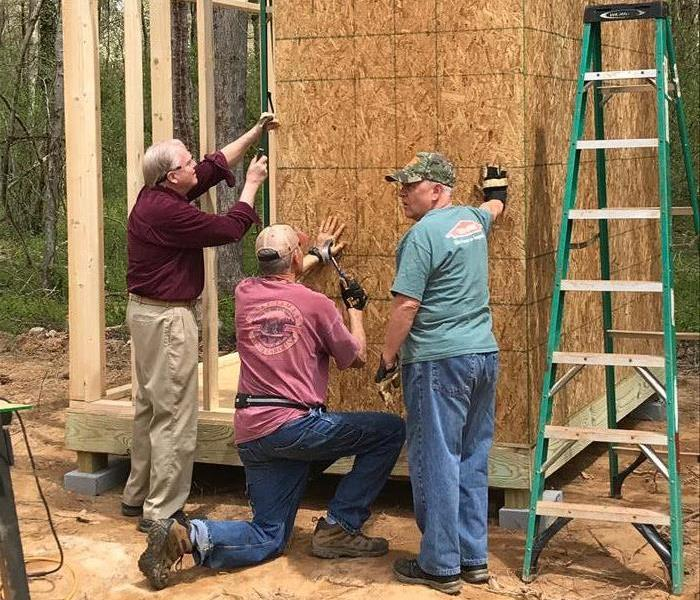 Three men hammering into the wooden frame of a shed