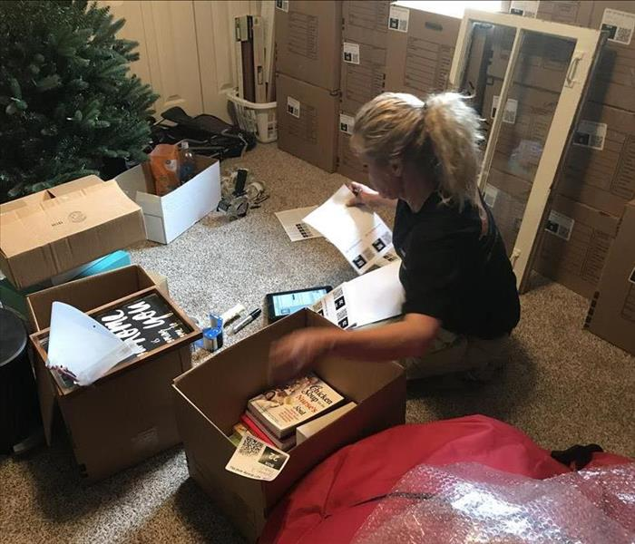 Sitting female SERVPRO employee places sticker on boxes filled with books