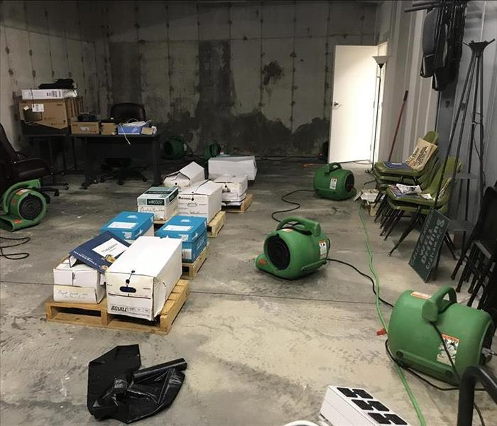 Green air movers drying water on concrete flooring in an office