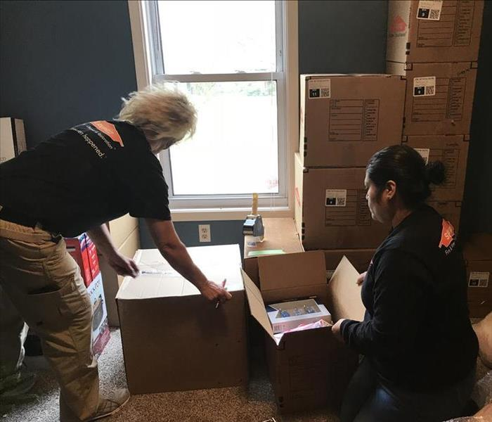 Two female SERVPRO employees pack items into cardboard boxes with SERVPRO logo