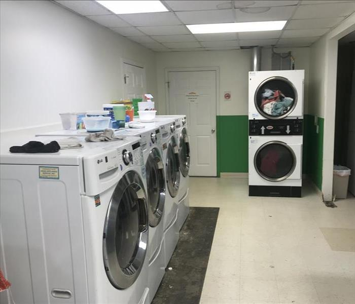 Row of white washing machines next to stacked dryers