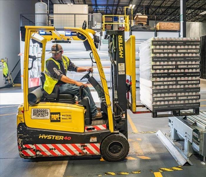 Man in yellow forklift lifts pallet in a warehouse